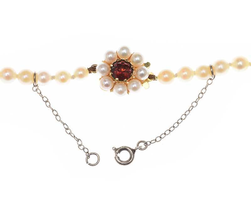 STRAND OF CULTURED PEARLS WITH 9CT GOLD GARNET AND PEARL CLASP at Ross's Online Art Auctions